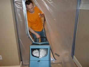 Water Damage Madison Technician Using Air Mover Near Vapor Barrier