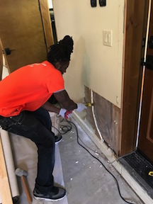 A Technician Repairing Water Damaged Drywall